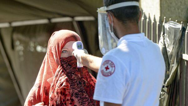 Zdravstveni radnik meri temperaturu ženi pre nego što joj odobri pristup spomen-groblju u Potočarima, blizu Srebrenice, Bosna, subota, 11. jul 2020.  - Sputnik Srbija