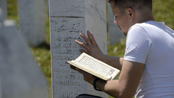 Човек се моли седећи између гробног камења у Поточарима, близу Сребренице, Босна, субота, 11. јули 2020. - Sputnik Србија