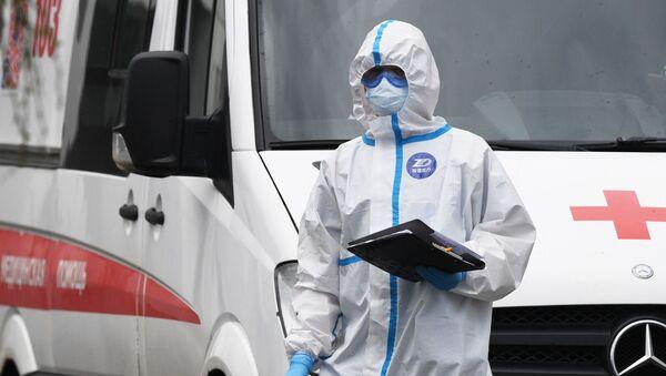Lekar u zaštitnom odelu ispred vozila hitne pomoći - Sputnik Srbija