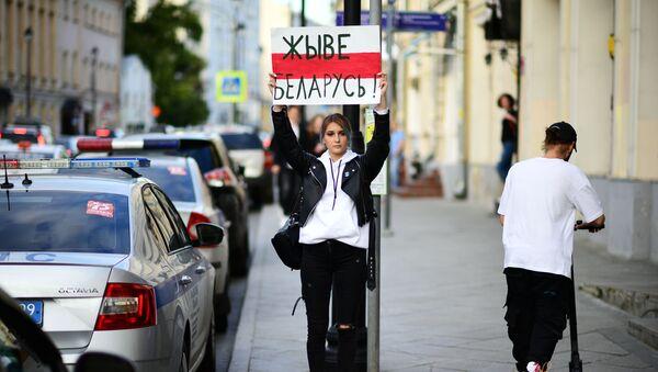 Девојка са плакатом испред амбасаде Белорусије у Москви - Sputnik Србија