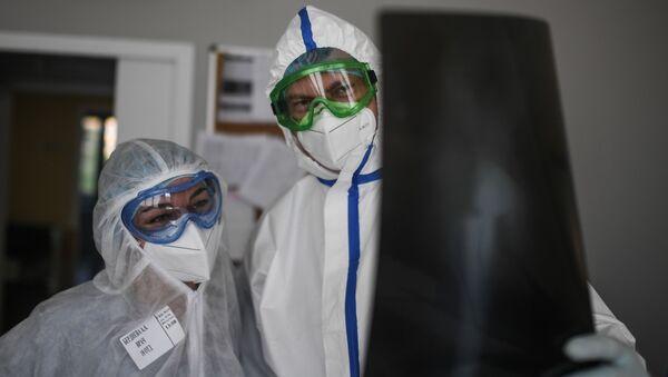 Lekari gledaju rentgentske snimke pacijenta sa kovidom 19 - Sputnik Srbija