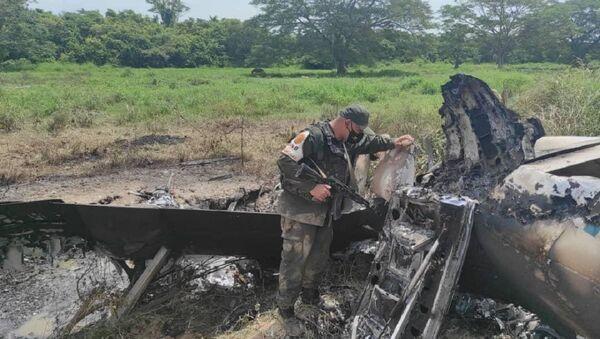 Венецуелански војник прегледава срушени авион са ознакама САД који је превозио кокаин. - Sputnik Србија