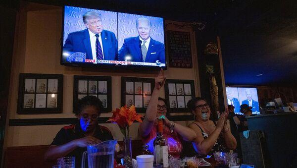 Посетиоци кафића у Калифорнији прате дебату двојице председничких кандидата, Доналда Трампа и Џоа Бајдена, на изборима у САД. - Sputnik Србија