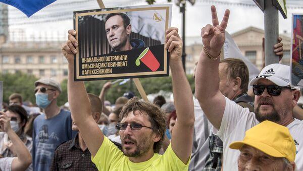 "Čovek drži plakat sa portretom Alekseja Navaljnog na kome stoji ""Navaljni je otrovan, znamo ko je kriv, Aleksej moraš da živiš"" - Sputnik Srbija"