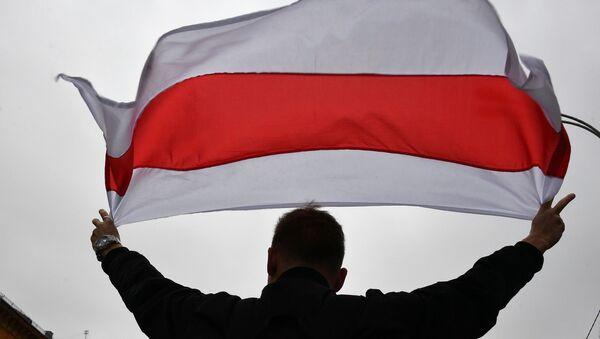 Učesnik protesta beloruske opozicije nosi zastavu - Sputnik Srbija