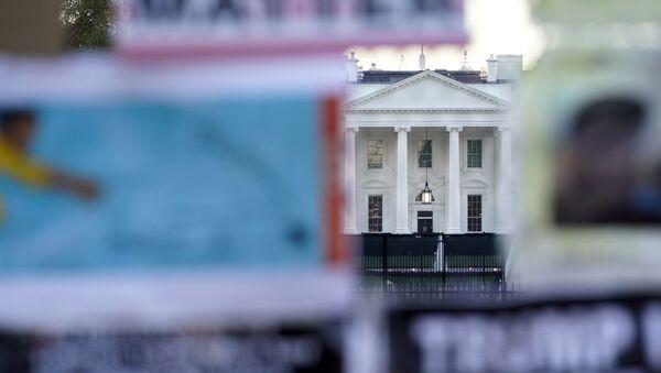 Бела кућа иза безбедносне ограде делимично прекривене протестним плакатима - Sputnik Србија
