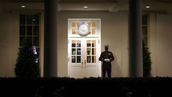 Амерички маринац стражари испред улаза у предворје Западног крила у Белој кући у Вашингтону - Sputnik Србија