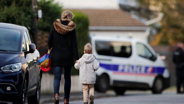 Žena drži dete za ruku na putu do škole u okolini koledža gde je Samuel Pati, učitelj francuskog, obezglavljen na ulicama pariskog predgrađa  - Sputnik Srbija