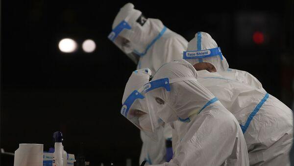 Medicinsko osoblje u zaštitnim odelima radi na trijažnoj kontrolnoj tački u Milanu - Sputnik Srbija