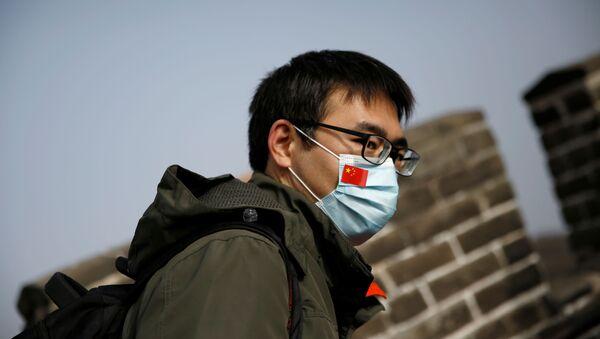 Човек на Кинеском зиду носи маску са кинеском заставом - Sputnik Србија