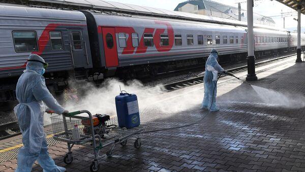 Pripadnici Ministarstva za vanredne situacije Rusije dezinfikuju peron na železničkoj stanici u Krasnojarsku - Sputnik Srbija