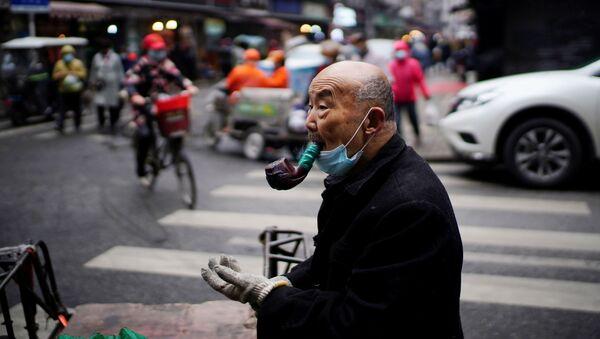 Gong Sinhua, 76, sa zaštitnom maskom, puši lulu na uličnoj pijaci skoro godinu dana nakon izbijanja pandemije u Vuhanu, provincija Hubej, Kina, 7. decembra 2020. godine. - Sputnik Srbija