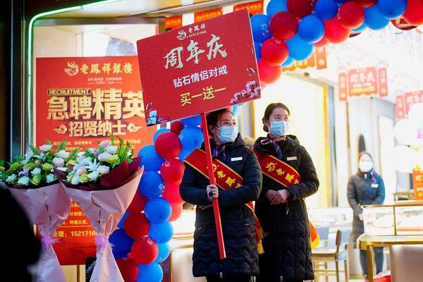 Prodajni pomoćnici draguljarnice nose maske za lice dok rade promocije u glavnoj šoping-zoni gotovo godinu dana nakon izbijanja pandemije u mestu Vuhan, provincija Hubej, Kina, 6. decembra 2020. - Sputnik Srbija