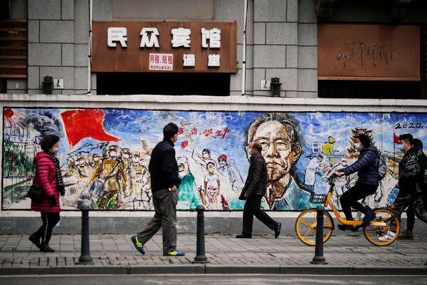 Ljudi nose maske za lice i šetaju se ulicom godinu dana nakon izbijanja pandemije u mestu Vuhan, provincija Hubej, Kina, 7. decembra 2020. - Sputnik Srbija