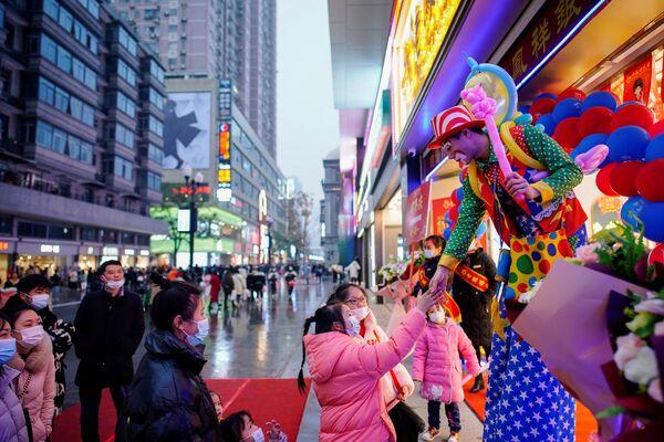 Klovn se pozdravlja sa ljudima tokom promocija u glavnoj šoping zoni  godinu dana nakon izbijanja pandemije u mestu Vuhan, provincija Hubej, Kina, 6. decembra 2020. - Sputnik Srbija
