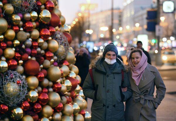 Prolaznici pored novogodišnje jelke ispred Skupštine grada Moskva na Tverskoj ulici u Moskvi.  - Sputnik Srbija
