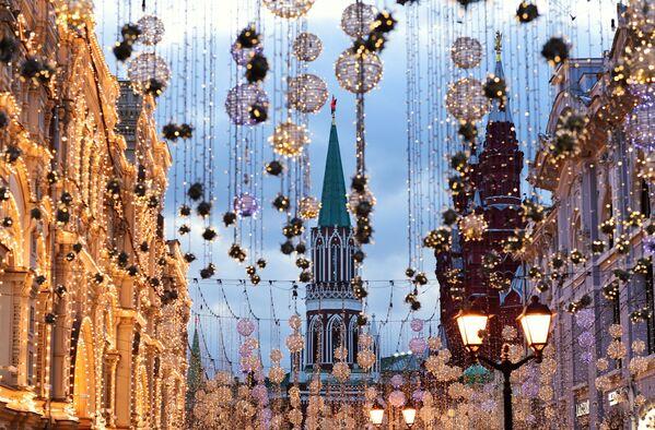 Pogled na Nikoljsku bašnju Kremlja u Moskvi kroz novogodišnje ukrase na Nikoljskoj ulici.  - Sputnik Srbija