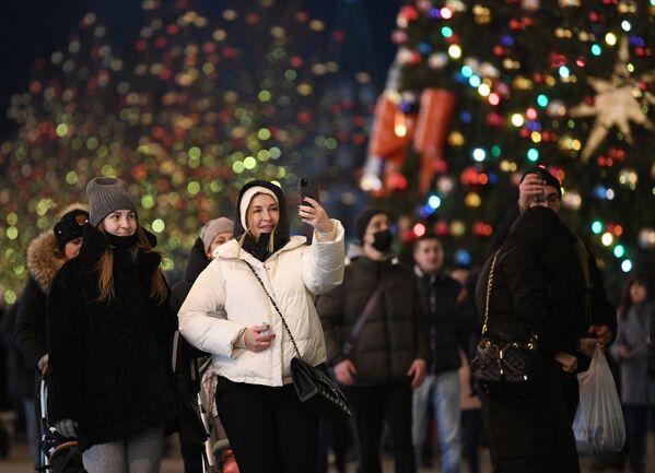 Prolaznici se fotografišu na ukrašenom Crvenom trgu u Moskvi.  - Sputnik Srbija
