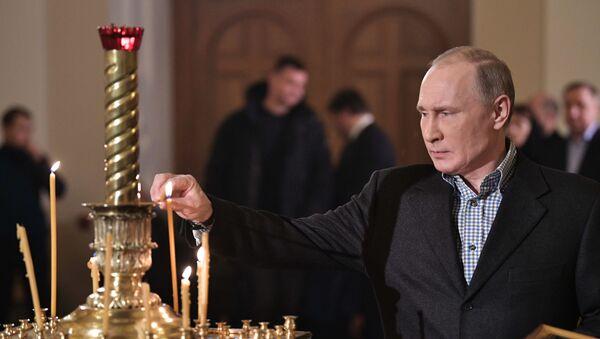 Председник Русије Владимир Путин пали свећу током божићне литургије у цркви Светог Симеона и Ане у Санкт Петербургу - Sputnik Србија