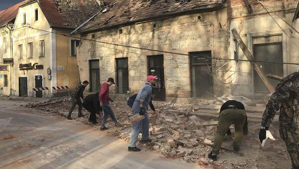 Становници уклањају остатке зграде оштећене у земљотресу, у Петрињи у Хрватској, у уторак, 29. децембра 2020. - Sputnik Србија