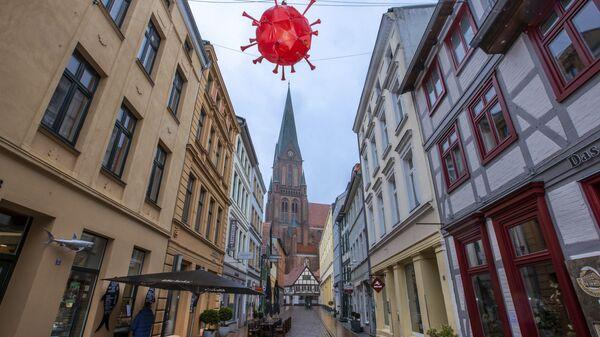 Maketa virusa korona iznad trgovačke ulice ispred katedrale u Šverinu tokom zaključavanja u Nemačkoj - Sputnik Srbija