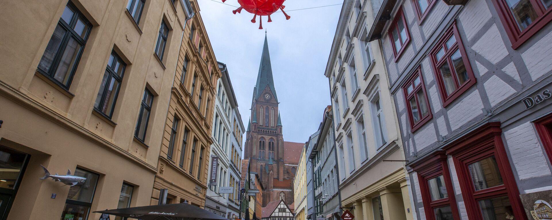 Макета вируса корона изнад трговачке улице испред катедрале у Шверину током закључавања у Немачкој - Sputnik Србија, 1920, 25.07.2021