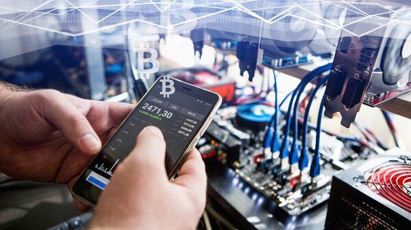 Čovek drži telefon sa prikazivanjem kursa bitkoina - Sputnik Srbija