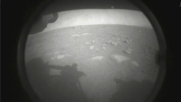 Слика коју је објавила америчка Национална управа за ваздухопловство и свемир. Прва фотографију коју је ровер снимио након историјског слетања на далеку црвену планету 18. фебруара 2021. године. - Sputnik Србија