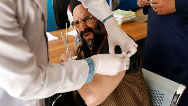 Работник больницы во время вакцинации AstraZeneca в Кабуле, Афганистан  - Sputnik Србија