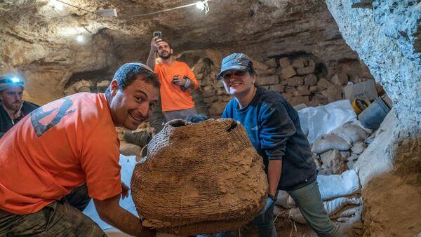 Izraelski arheolozi sa drevnom korpom pronađenom u pećini Murabat u Judejskoj pustinji nedaleko od Mrtvog mora - Sputnik Srbija