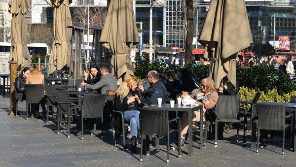 Одлуку Кризног штаба, да угоститељским објектима дозволи шалтерску продају хране и пића, Београђани су искористили да уз кафу за понети уживају на пролећном сунцу. - Sputnik Србија