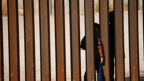 Dete migrant prolazi kroz zid na granici SAD i Meksika - Sputnik Srbija