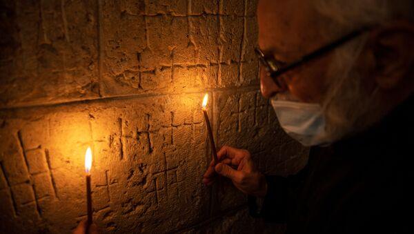 Otac Samuel Agojan, jermenski sveštenik u crkvi Hramu groba Gospodnjeg drži sveće za osvetljavanje krstova urezanih u drevni kameni zid kapele Svete Jelene unutar crkve koja je u hrišćanskoj tradiciji poštovana kao mesto Isusovog raspeća i sahrane - Sputnik Srbija