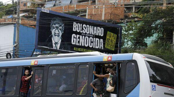 Putnici u prepunom autobusu pored bilborda protiv brazilskog predsednika Bolsonara i njegove politike u pandemiji - Sputnik Srbija