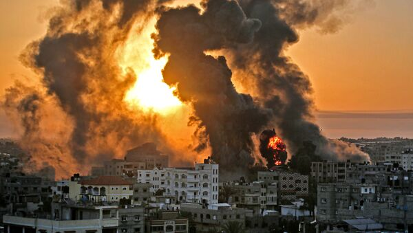 A fire rages at sunrise in Khan Yunish following an Israeli airstrike on targets in the southern Gaza strip, early on May 12, 2021. - Israeli air raids in the Gaza Strip have hit the homes of high-ranking members of the Hamas militant group, the military said Wednesday, with the territory's police headquarters also targeted. (Photo by YOUSSEF MASSOUD / AFP) - Sputnik Србија