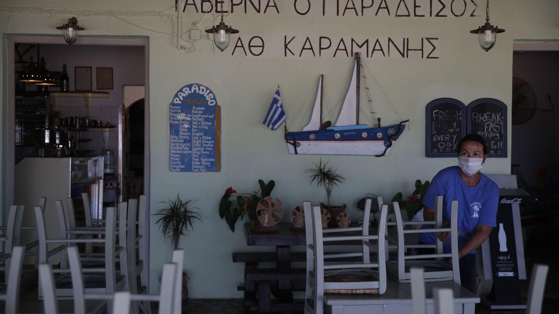 Радник поставља столице у таверни на плажи Плака у егејском острву Наксос - Sputnik Србија, 1920, 26.05.2021