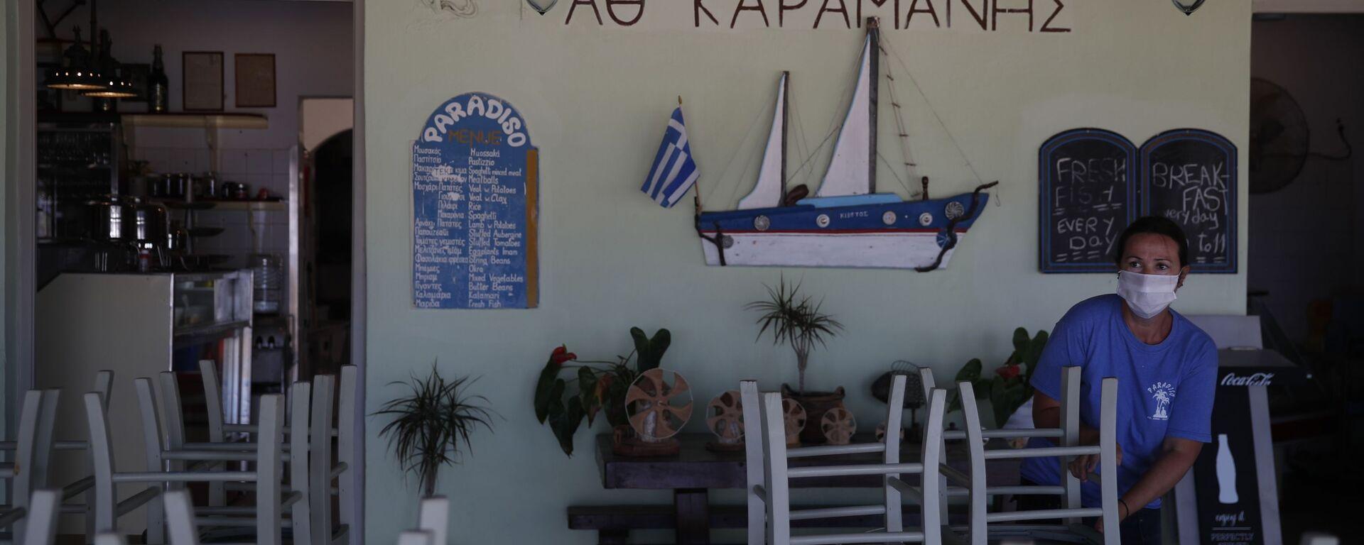 Radnik postavlja stolice u taverni na plaži Plaka u egejskom ostrvu Naksos - Sputnik Srbija, 1920, 26.05.2021