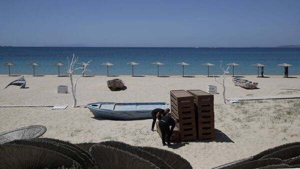 Radnici uređuju ležaljke i postavljaju suncobrane na plaži Plaka na egejskom ostrvu Naksos - Sputnik Srbija
