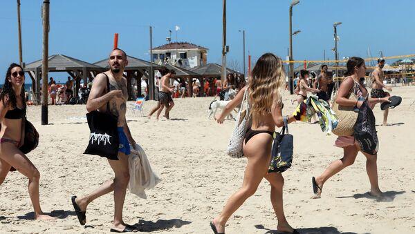 Izraelci beže sa plaže u Tel Avivu posle oglašavanja sirena za vazdušnu opasnost usled raketa ispaljenih iz Pojasa Gaze - Sputnik Srbija