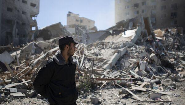 Палестинци полицајац испред рушевина - Sputnik Србија
