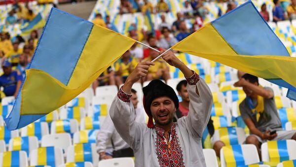 Украјински фудбалски навијач са заставама Украјине - Sputnik Србија