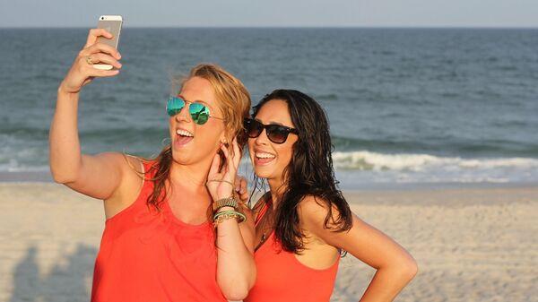 Девојке са мобилним телефоном на плажи - Sputnik Србија