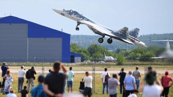 Зрители наблюдают за пролетом многофункционального истребителя пятого поколения Су-57 во время летной программы на МАКС-2021 - Sputnik Србија
