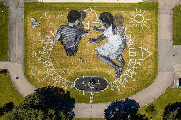 Слика у стилу ленд-арта француског сликара Сајпа у парку Уједињених нација у Женеви - Sputnik Србија