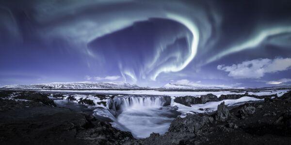 Ова слика приказује зимску аурору на једном од најпрепознатљивијих водопада на Исланду - водопад богова, моћни Goðafoss. Температура је била око минус 10 степени, мирно и ведро време са пуним месецом невероватно је осветлило подручје, што је знатно олакшало стварање слике.Прелепе нијансе Месеца, помешане са поларном светлошћу и мешавином полузалеђеног водопада, и снопови светлости по небу учинили су ову ноћ незаборавном за фотографа.Goðafoss, Исланд, 6. фебруара 2020. - Sputnik Србија