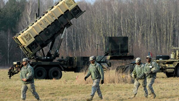 U.S soldiers walk next to a Patriot missile defence battery during join exercises at the military grouds in Sochaczew, near Warsaw - Sputnik Србија