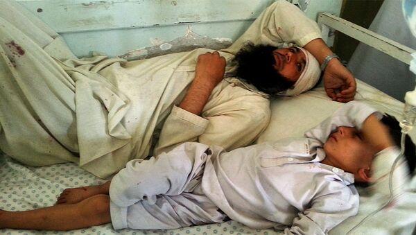 Авганистанац и дете леже на кревету након што су рањени у експлозији у провинцији Кунар, Авганистан, у недељу, септембар 20, 2015. - Sputnik Србија