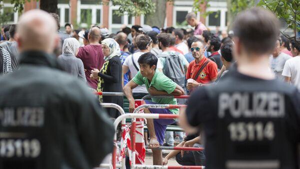 Policija stoji pored azilanata koji čekaju ispred prihvatnog centra za izbeglice u Berlinu, Nemačka, petak, 7. avgusta, 2015. - Sputnik Srbija