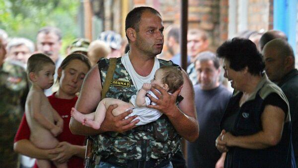Припадник руске специјалне службе носи бебу након терористичког напада у Беслану - Sputnik Србија