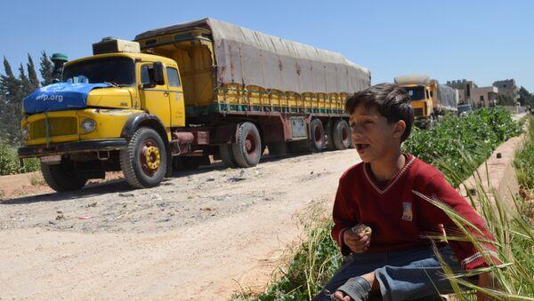 Sirijski dečak jede dok pored njega prolazi konvoj kamiona Svetskog programa za hranu i Unicefove međunarodne pomoći u okolini grada Homsa, 21. april 2015. - Sputnik Srbija